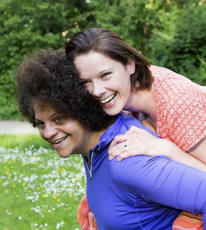 lesbianas: dos mujeres en el parque de abrazos y riendo