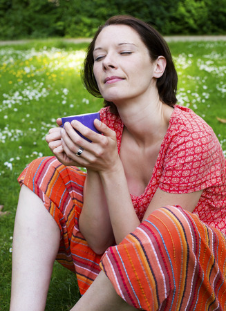 young woman sitting in park and holding a cup photo