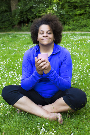 woman sitting in park and holding a cup photo
