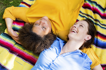two woman lying on a blanket in a park and hugging each other Stock Photo