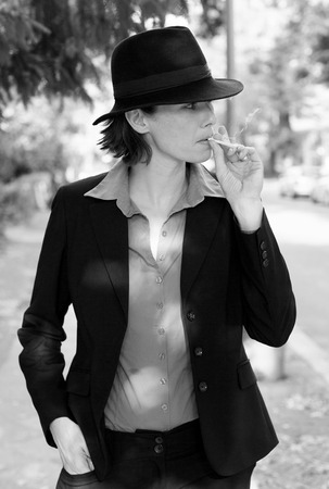 butch: woman in suit and hat is smoking a cigarette