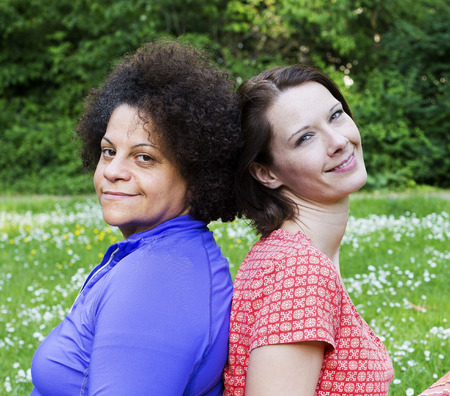 two women leaning to ech other in park photo
