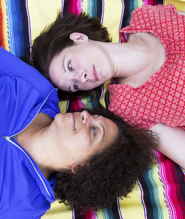 two women lying on a blanket and looking at each other photo