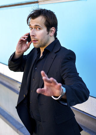 interrupted: businessman on the phone giving a sign with his hand to be not interrupted Stock Photo