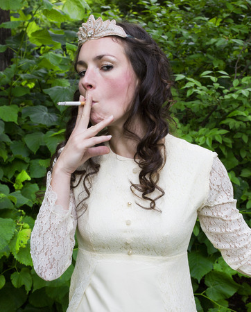 princess in a gown wearing a crown is smoking a cigarette photo