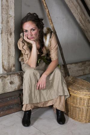brunette woman dressed as cinderella looking sad photo