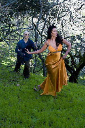 brunette woman being chased by a zombie in a garden photo