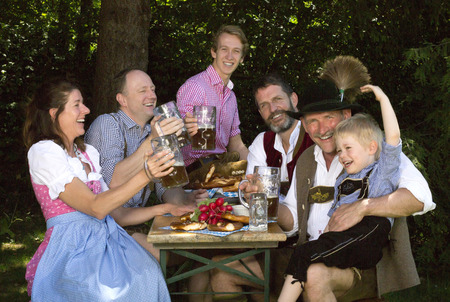 biergarten: bavarian family sitting outside on a bench and drinking beer Stock Photo
