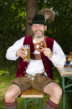 bavarian man sitting on bench with a beer mug