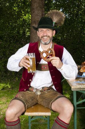 Beierse man zittend op de bank met een pul bier Stockfoto - 29936567