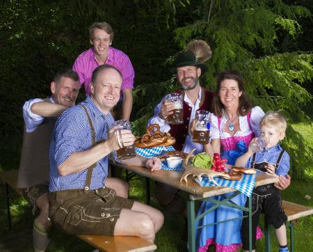 Beierse familie buiten zitten op een bankje en het drinken van bier Stockfoto