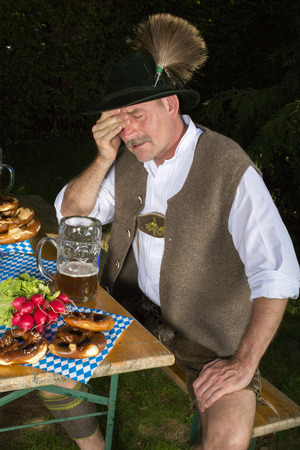 inebriated: bavarian man sitting on bench with a beer mug and is drunk Stock Photo