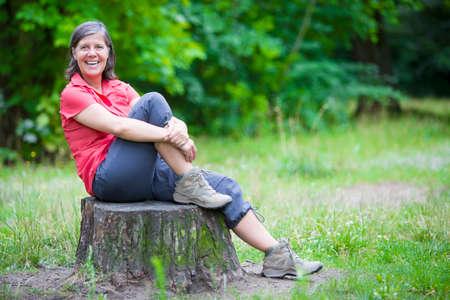 oudere vrouw zittend op een boomstronk en glimlacht