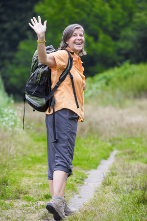 older woman is hiking in nature photo