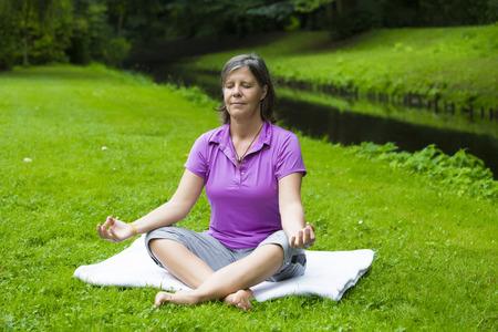 oudere vrouw in het park door een rivier doet yoga