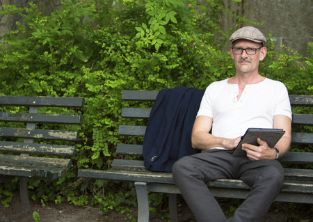 man sitting on a bench in a park with tablet in his hand photo