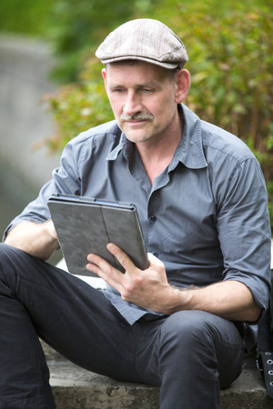 man sitting by the water with tablet in his hand photo