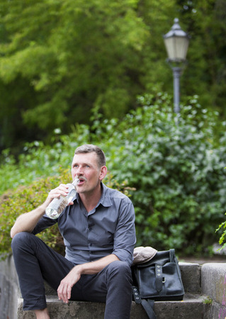 man drinking water: man sitting in park and drinking water