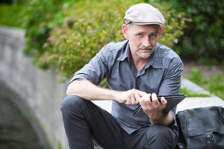 man zat bij het water met tablet in zijn hand