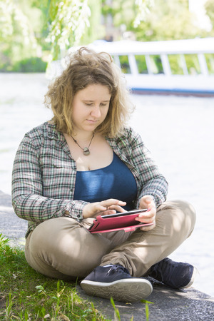 overweight students: young woman sitting in park by the water with a tablet in her hands Stock Photo