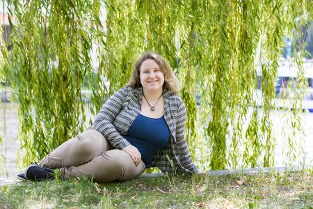 公園の水辺に座っていた金髪女性