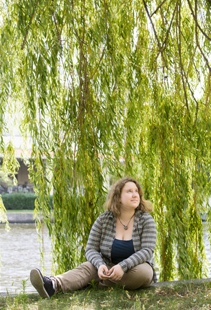 overweight students: young blond woman sitting by the water in a park