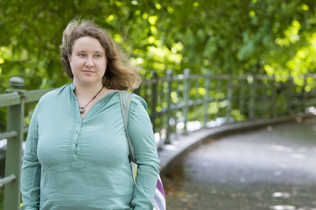 overweight students: young blond woman standing in park and looking thoughtfully