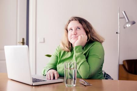 jonge vrouw zit op een bureau met laptop Stockfoto