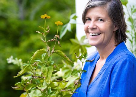 mujeres mayores: retrato de una mujer mayor en su balcón y sonriendo