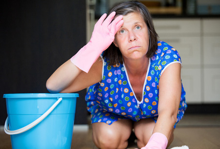 fregando: Mujer fregando el suelo y mirando agotado