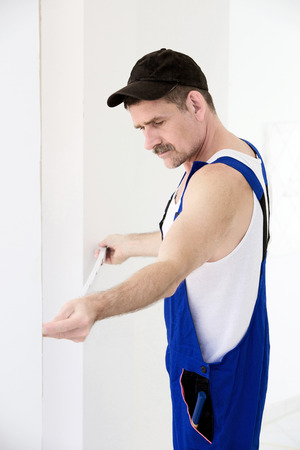 handyman holding a measure tape to a wall photo