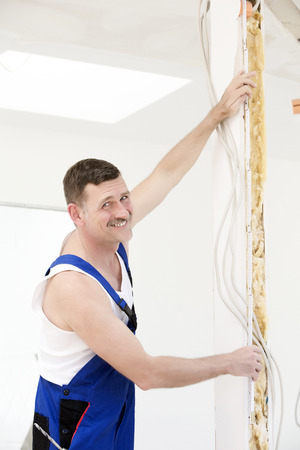 handyman holding a measure tape to a wall and smiles photo