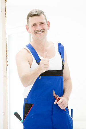 repairman standing with pliers in his hand and thumbs up photo