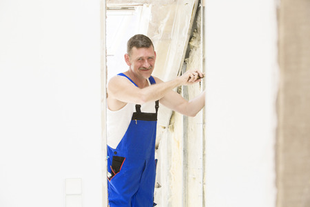 repairman with screwdriver in his hand working on a wall and smiles photo
