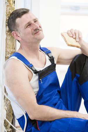 repairman having a break and eating a sandwich photo