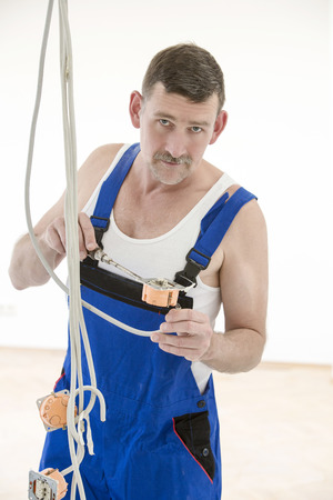 electrician in a boilersuit is working on a cable photo