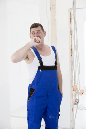 repairman in a boilersuit is yawning photo