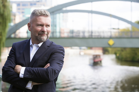 businessman in a suit standing in front of a bridge