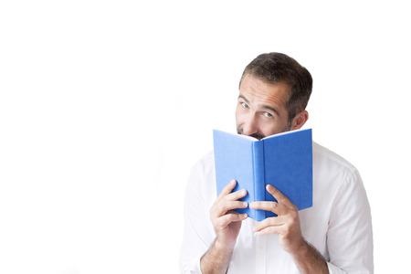 man in a white shirt reading a book photo