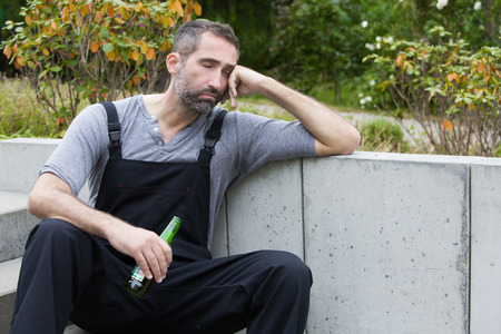 workman sitting outside with a bottle of beer and sleeping photo