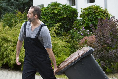 man picking up a trashcan on the street
