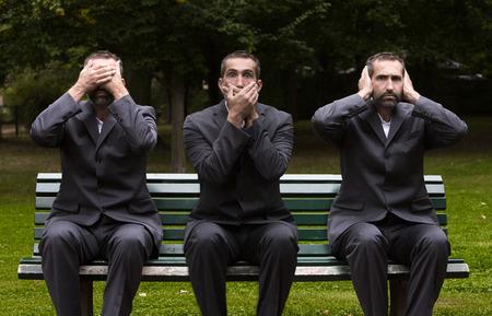 3 回彼の耳、目と口を覆っているベンチに座っている実業家