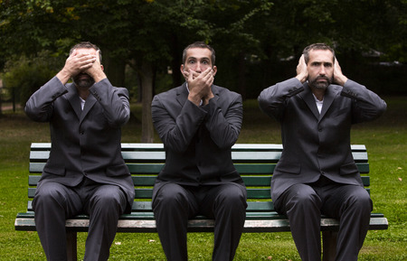 escuchar: hombre de negocios sentado en un banco de tres veces que cubren las orejas, los ojos y la boca Foto de archivo