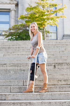blonde woman with crutches standing on stairs photo