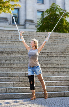 blonde woman with crutches standing in front of stairs photo