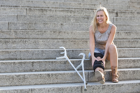 immobility: blonde woman with crutches sitting on stairs Stock Photo
