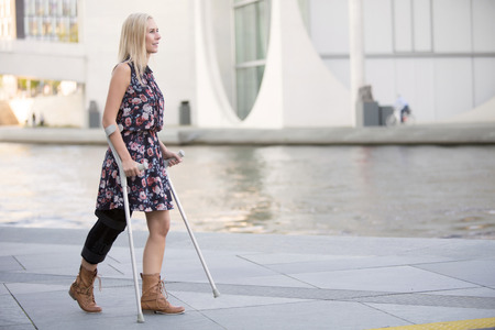 blonde woman in a dress walking with crutches Stock Photo