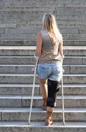 blonde woman with crutches walking on stairs photo