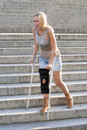 blonde woman with crutches walking on stairs