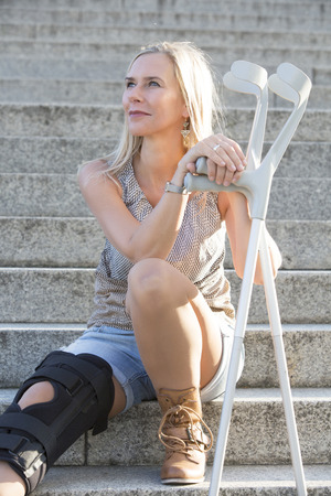 blonde woman with crutches sitting on stairs photo